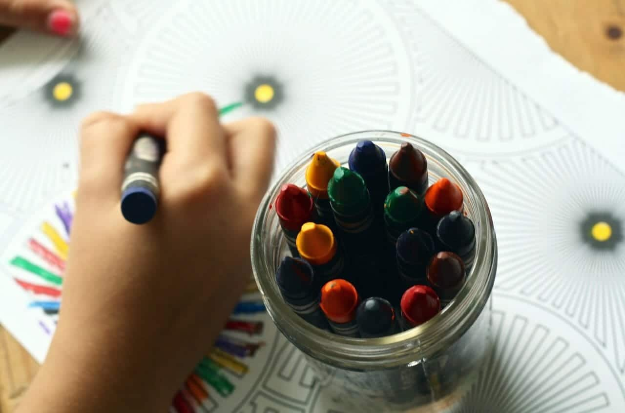 jar of crayons and child coloring