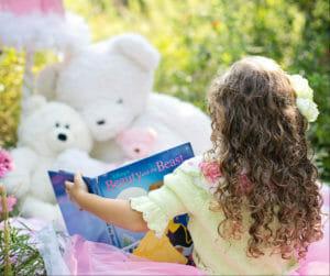preschool girl reading to stuffed animals