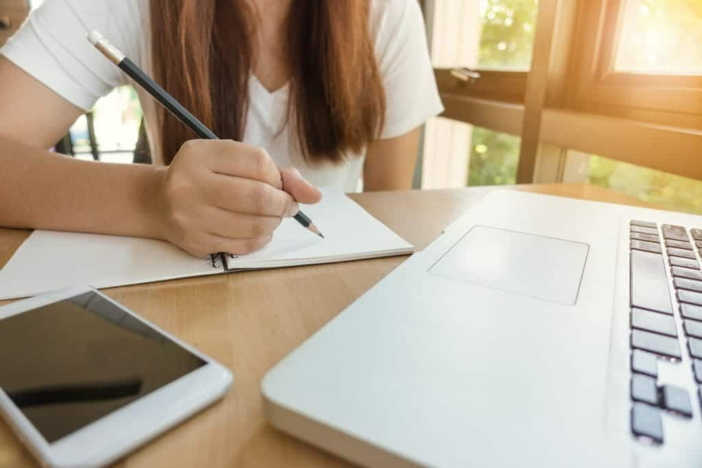 girl writing with laptop