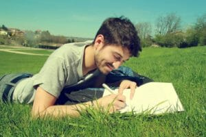 young man sitting in grass writing