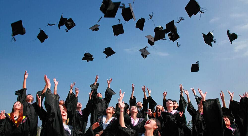 Highschool graduates tossing their caps in the air