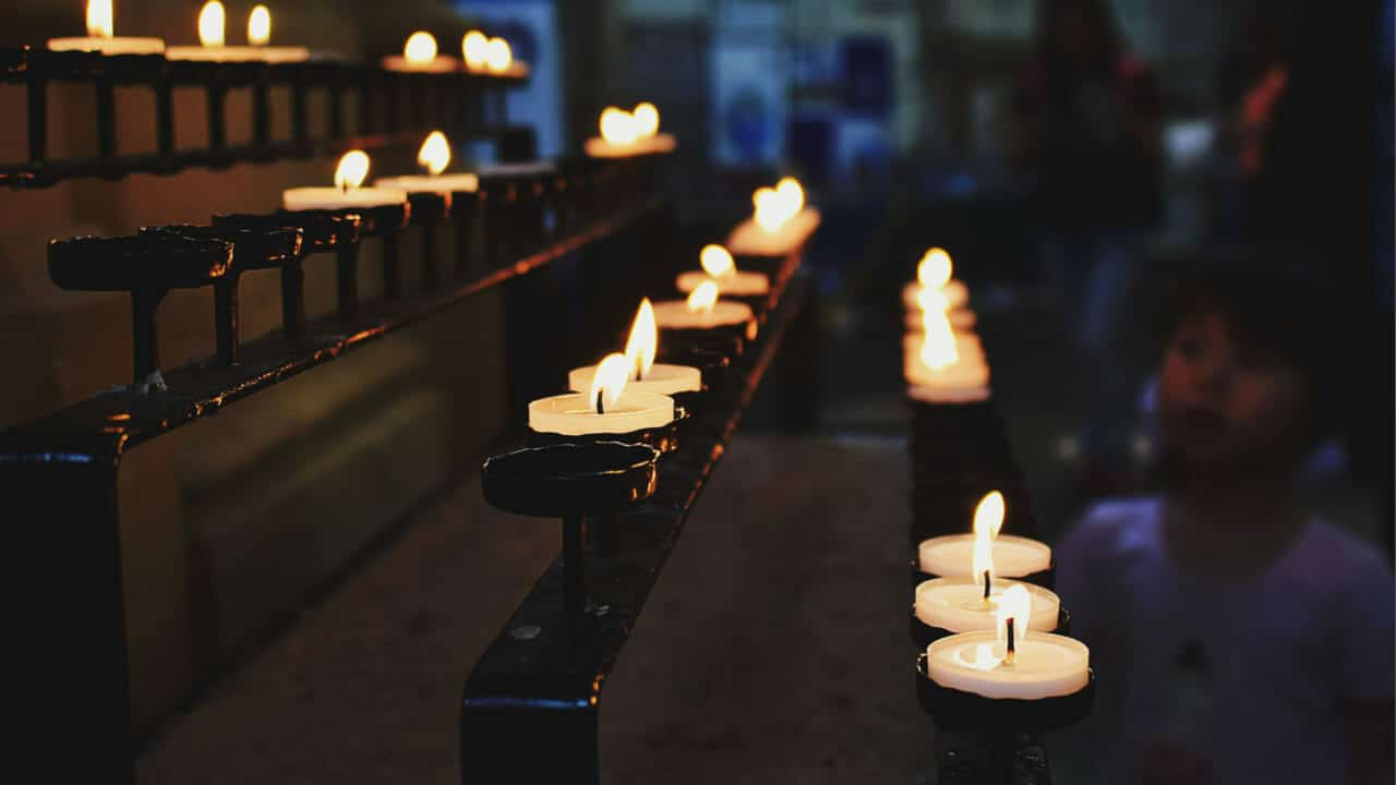burning candles in church and people praying