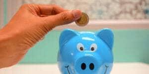 Hand putting a coin in a piggy bank