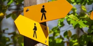 Yellow trail sign showing arrows pointing 2 different directions