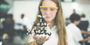 High school girl in science lab holding molecular model