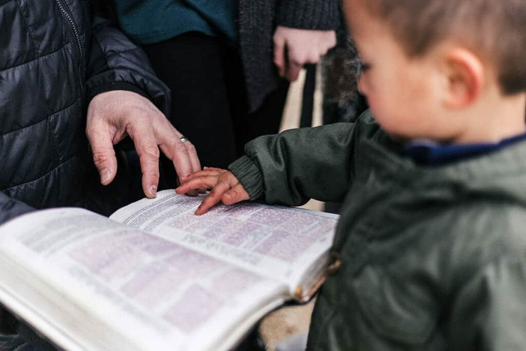 Parent and Child holding hands on the Bible