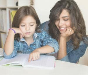 Homeschool and mother reading a book together