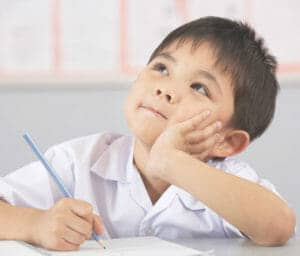 Little boy thinking about what he is going to write