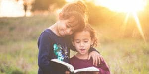 2 young girls reading the Bible together