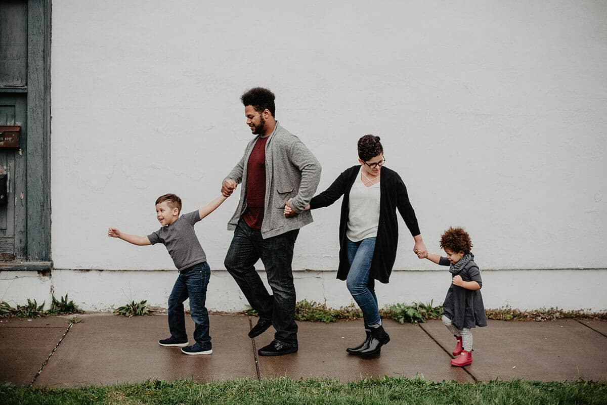 Family holding hands and walking in the rain together
