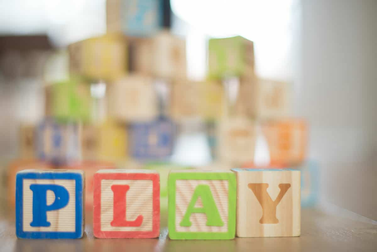 """""""Play"""" spelled out with alphabet blocks"""