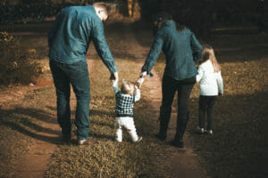 Family of 4 walking together outside and holding hands